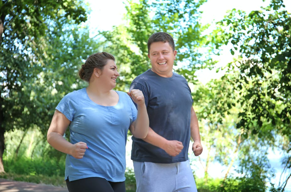 Man and woman exercising outdoors.