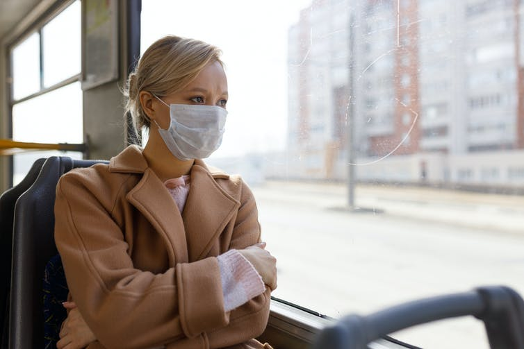 A woman in a surgical mask looks out of a train window