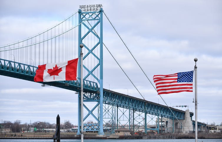 A Canadian flag and an American flag in the foreground with a suspension bridge over a river behind them.