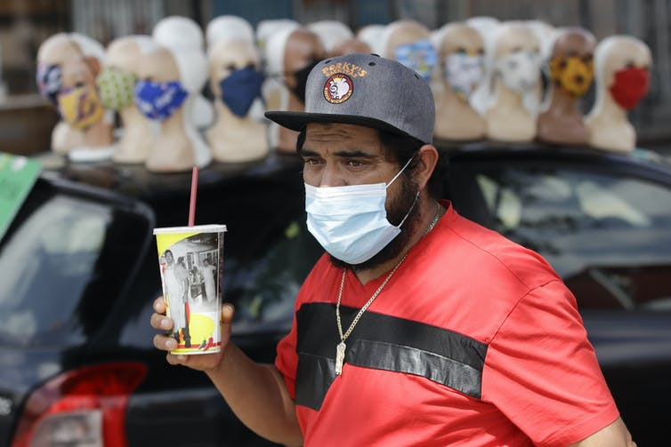 A man in a red shirt holding a soda while wearing a mask in front of a display of mannequins all wearing masks