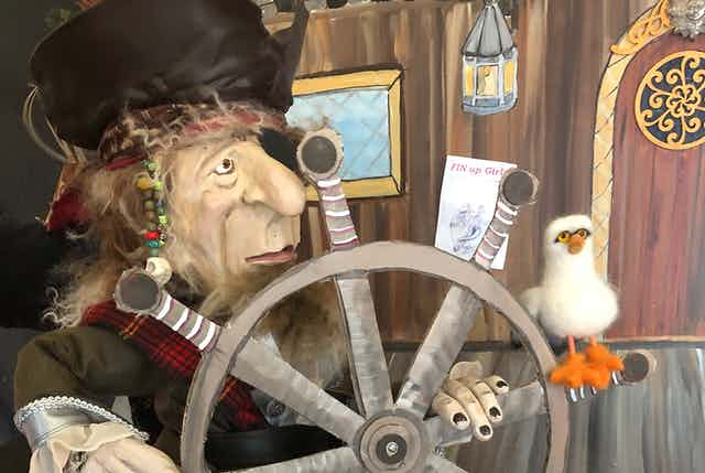 A pirate puppet holds a ship's steering wheel and a seagull puppet is perched on it.