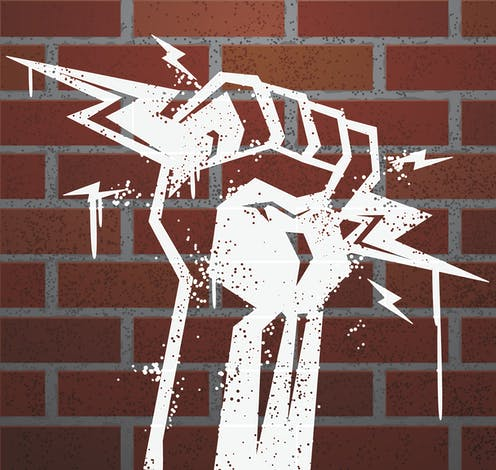 stencil of fist holding lightning bolts with brick background