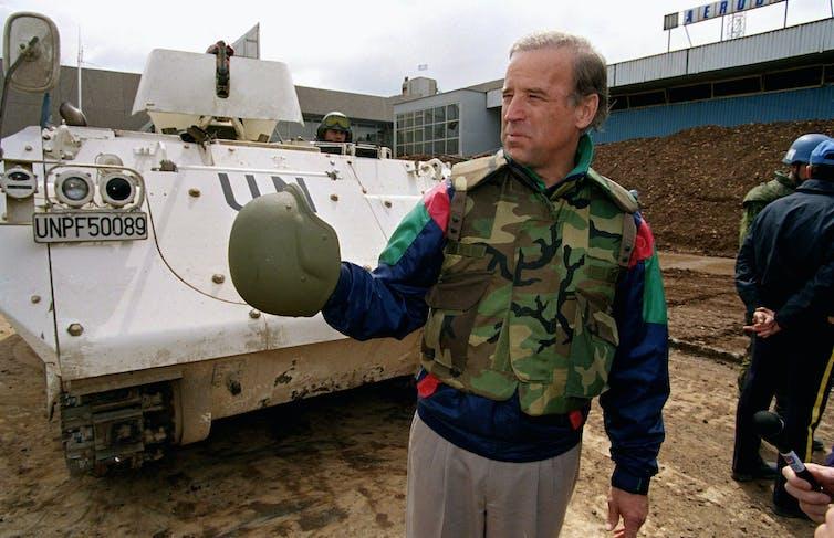 Joe Biden in Bosnia wearing camouflage and standing near a tank
