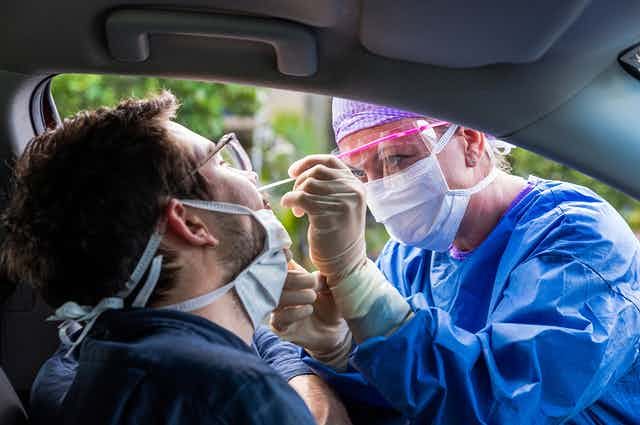 Healthcare worker taking a nasal swab from man sitting in car