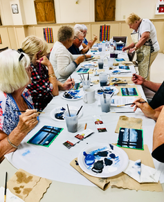 Older adults at a long table working on art projects.