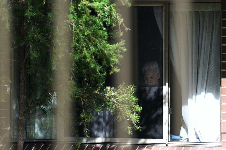 Resident of Newmarch House aged care facility looks out her window during the COVID-19 pandemic.