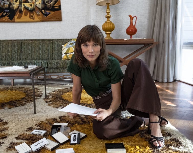 Tilda Cobham-Harvey as Helen Reddy sits on a shag rug surrounded by cassette tapes