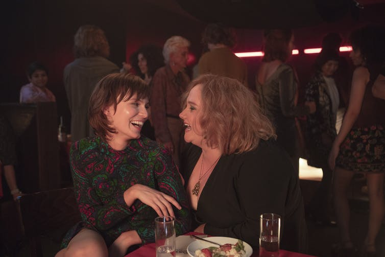 Movie still, Helen sits in Lillian's lap at a bar as they laugh.