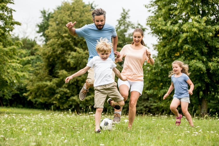 A family (dad, mum, son and daughter) playing soccer in a field.