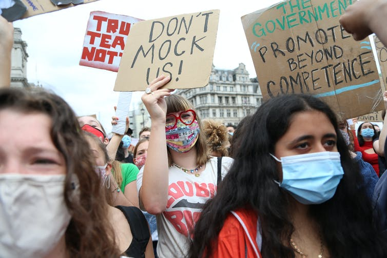Teenage protestors wearing masks and holding signs.