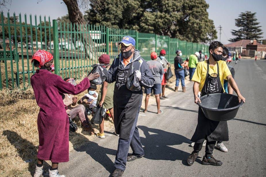 Volunteers distribute food parcels