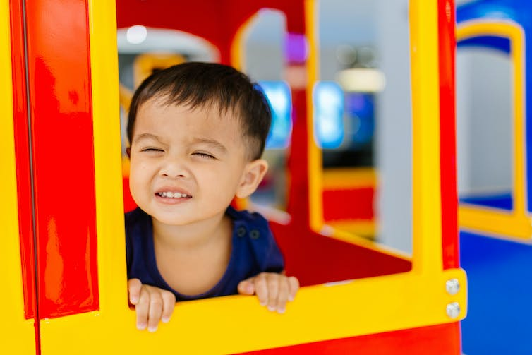 Young boy playing in a cubby house.
