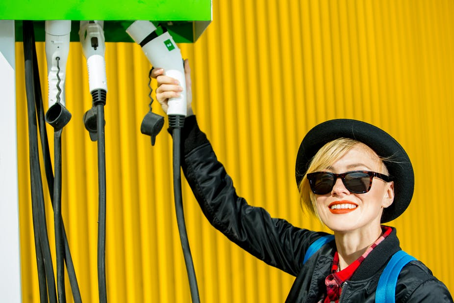 Smiling woman holding electric vehicle charger.