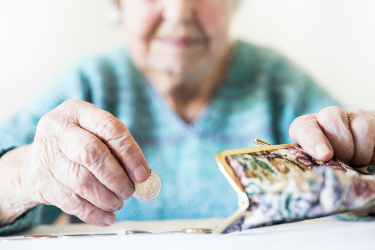 Elderly woman counting the money in her purse.