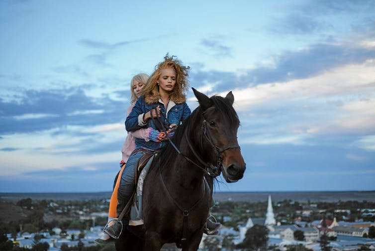 Two young women on a horse riding away from a small South African town.