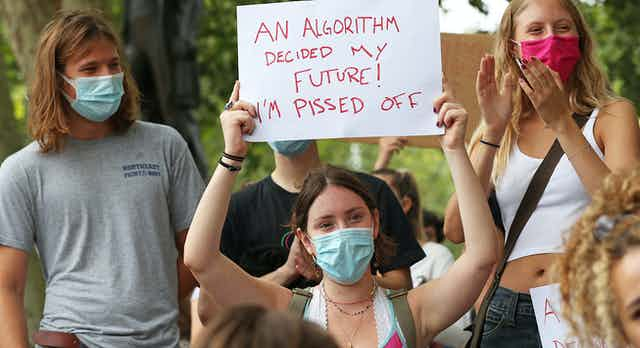Young woman in protest group holds up sign.