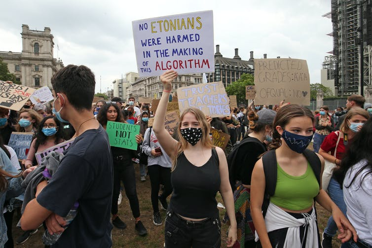 Teenagers marching in protest holding signs