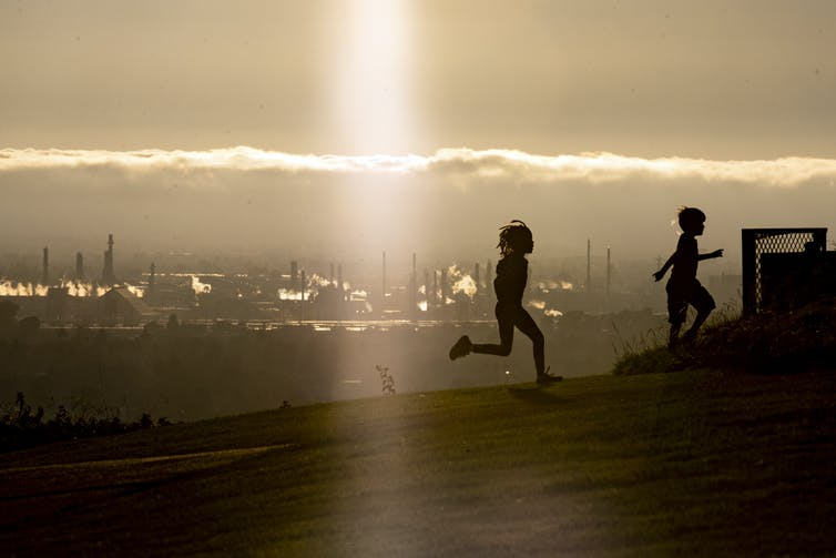 Two children running on a hill, oil refinery in background.