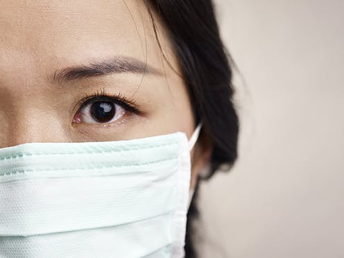 Close-up of the left side of a woman's face wearing a face mask. Her eye is bloodshot.