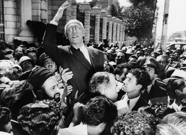Prime Minister Mohammad Mosaddegh rides on the shoulders of cheering crowds in Tehran's Majlis Square in 1951.