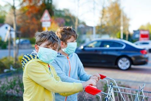 Dos hermanos muy parecidos con mascarillas empujan un carro de supermercado.