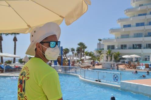 Un socorrista de piscina, con sombrero, mascarilla y gafas de sol.