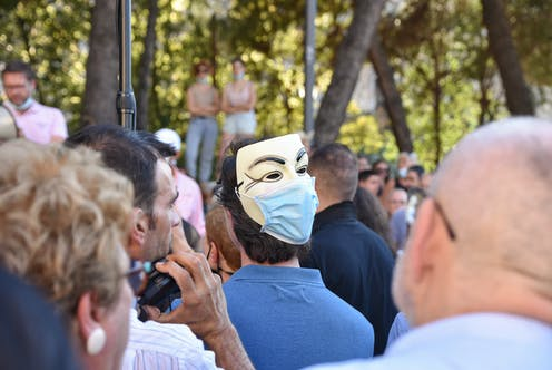 Un hombre porta una máscara de Anonimous con mascarilla quirúrgica.