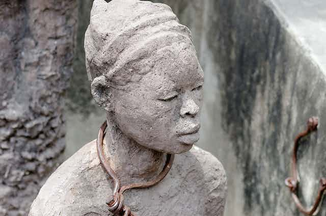 A statue of a woman with a chain around her neck.