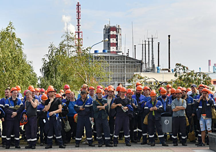 Belarusian workers in orange hardhats stand with arms crossed in front of a factory