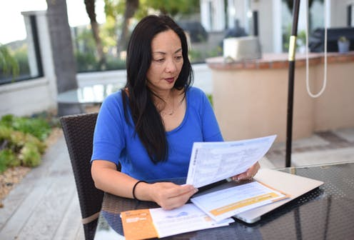 A woman at home holding an absentee ballot.