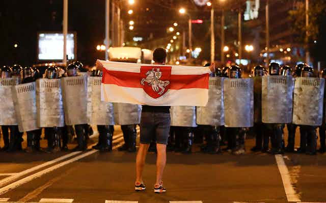 A sole man holding the Belarussian flag faces a line of police in riot gear