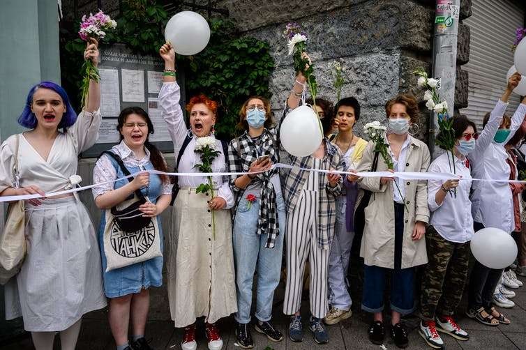 Women dressed in white stand in a line and shout while carrying flowers and balloons