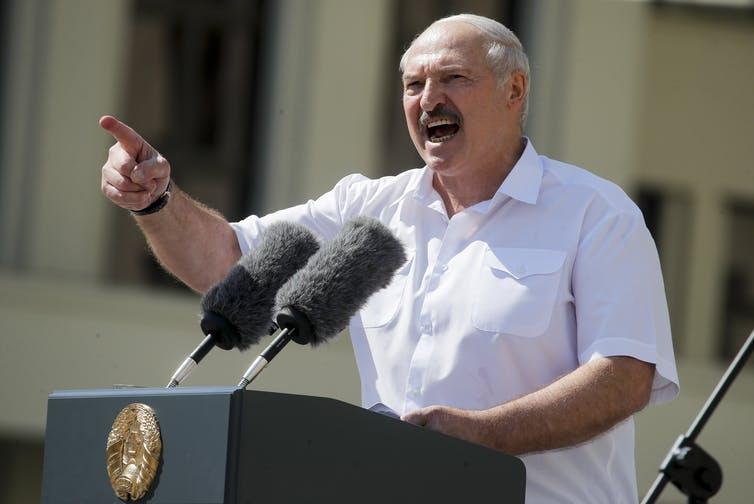 The Belarusian president at a podium, speaking and pointing