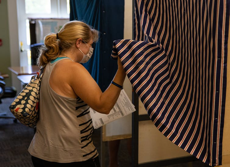 A women pulls back a curtain to enter a voting booth.