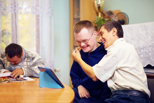 Two men with intellectual disability laughing while watching an iPad.
