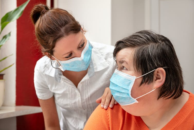 A carer has her hand on the shoulder of a woman with disability. Both are wearing masks.