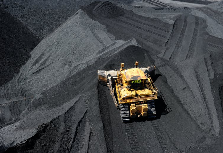 Machinery working in a coal pile