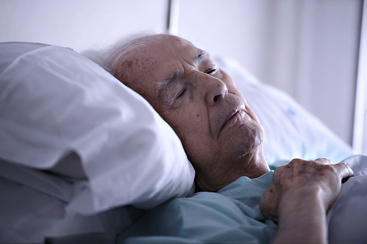 Elderly man lies resting in bed.