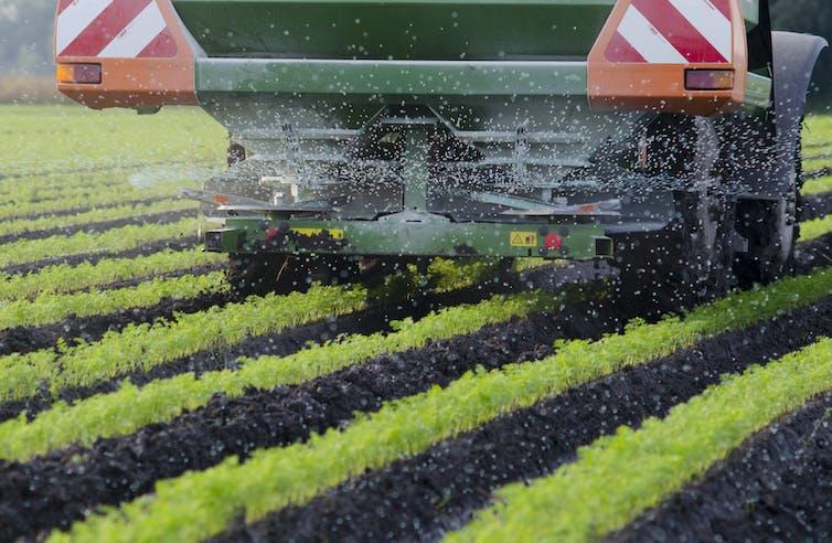 Farm machinery spreading fertiliser