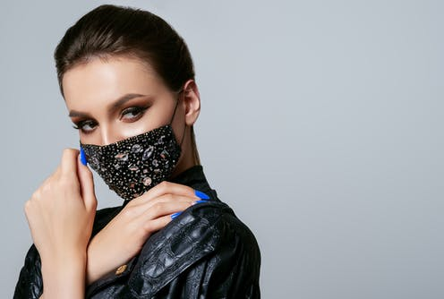 Glamorous woman wears bejewelled face mask