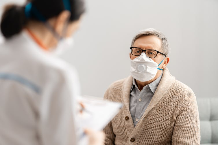 An elderly gentleman wearing a mask is attended to by a nurse.