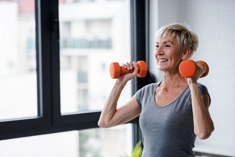 An elderly lady lifting some small weights at home