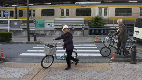 People on bicycles near a railway line in a Japanese city.