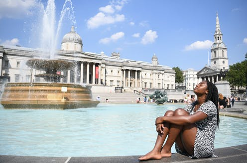 A woman sits beside a fountain in sunny London.