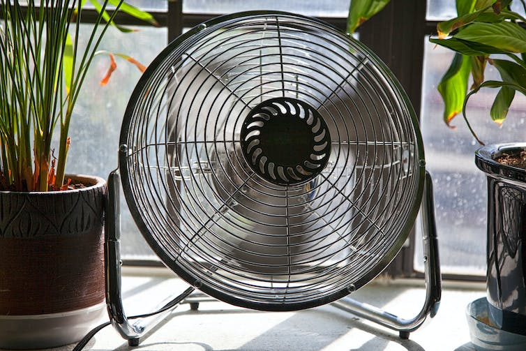 A spinning fan sits on a windowsill.