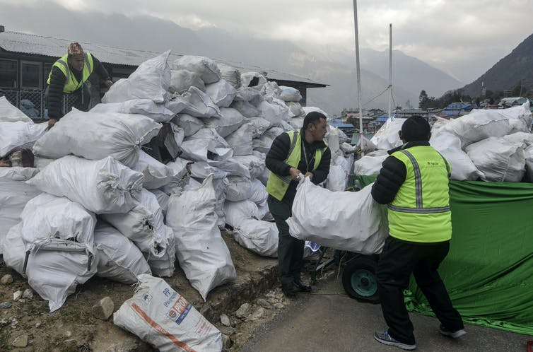 Men loading bags of rubbish onto vehicle.