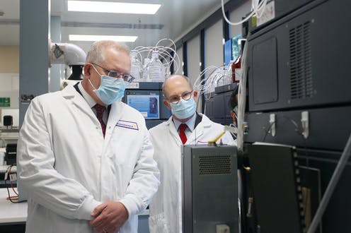 Scott Morrison and Paul Kelly, wearing lab coats, in a laboratory