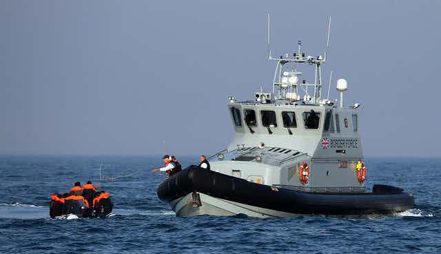 A UK Border Force boat meets a small boat in the English Channel.