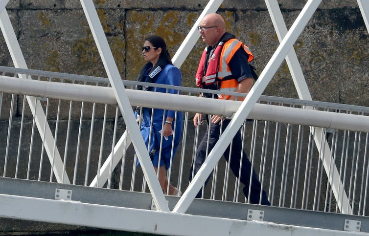Priti Patel walks with a man in a life jacket.