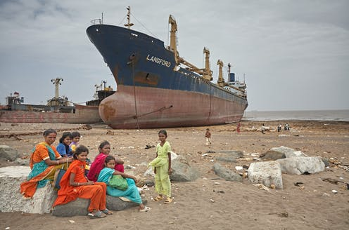 A group of women sit on a beach in front of a cargo ship.